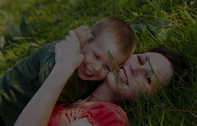 Mum hugging son in grass